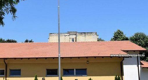 Catarg cu drapel ridicat de militari și cercetași în curtea Școlii Octavian Goga